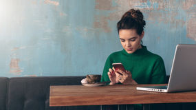 坐在咖啡馆的桌上和使用智能手机的年轻微笑的女商人 在桌上是膝上型计算机和咖啡 免版税库存图片