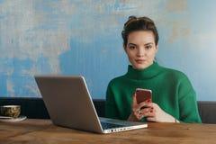 坐在咖啡馆的桌上和看照相机的年轻微笑的女实业家,当拿着智能手机时 库存照片