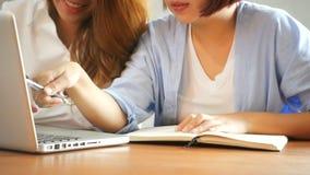 坐在咖啡馆的桌上的两个年轻女商人 用膝上型计算机和咖啡的亚裔妇女 股票视频