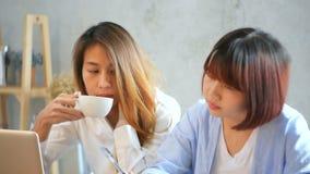坐在咖啡馆的桌上的两个年轻女商人 用膝上型计算机和咖啡的亚裔妇女 股票录像