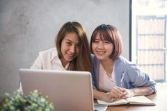 坐在咖啡馆的桌上的两个年轻女商人 用膝上型计算机和咖啡的亚裔妇女 工作在咖啡店的自由职业者 免版税库存图片