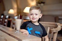 坐在咖啡馆的桌上的小男孩饮用的奶昔 免版税库存图片