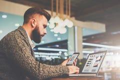 坐在咖啡馆的桌上,拿着智能手机和使用有图的有胡子的商人膝上型计算机,图表在屏幕上 图库摄影