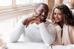 坐在咖啡馆的欢悦非裔美国人的夫妇 图库摄影