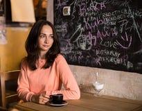坐在咖啡馆的沉思妇女 库存照片