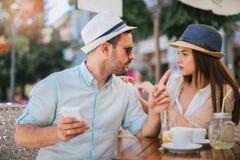 坐在咖啡馆的爱的夫妇享用在咖啡和使用电话 库存图片