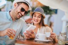 坐在咖啡馆的爱的夫妇享用在咖啡和使用电话 免版税库存图片