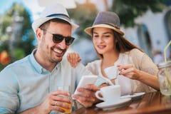 坐在咖啡馆的爱的夫妇享用在咖啡和使用电话 免版税库存照片