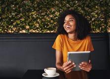 坐在咖啡馆的笑的年轻女人 免版税库存照片