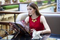坐在咖啡馆的美丽的女孩和考虑菜单 免版税库存照片