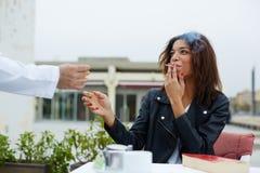 坐在咖啡馆的美丽的女孩要求侍者点燃香烟 库存照片