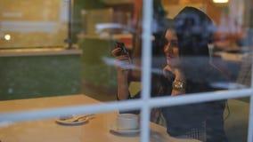 坐在咖啡馆的美丽的妇女在窗口和使用您的电话 股票录像