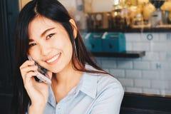 坐在咖啡馆的聪明的女商人使用手机 免版税图库摄影