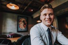 坐在咖啡馆的英俊的微笑的办公室人 库存照片