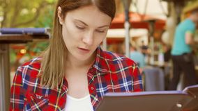 坐在咖啡馆的饥饿的妇女看菜单 在餐馆的微笑的美丽的女性选择食物 影视素材
