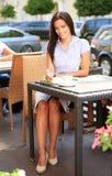 坐在咖啡馆的年轻专业女实业家 免版税库存图片
