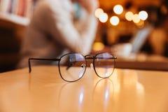 坐在咖啡馆的年轻人 在镜片的焦点 免版税库存照片
