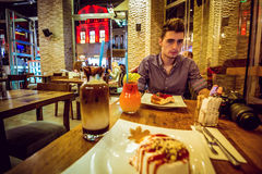 坐在咖啡馆的年轻人 免版税库存照片