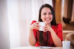 坐在咖啡馆的年轻可爱的妇女 免版税库存照片