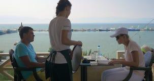 坐在咖啡馆的年轻夫妇,女服务员接受从妇女,学习菜单的人的命令 股票视频