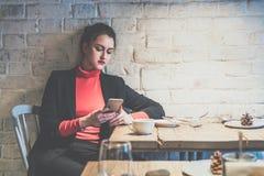 坐在咖啡馆的年轻女实业家在木桌和用途智能手机上 在桌咖啡上 免版税图库摄影