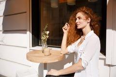 坐在咖啡馆的年轻美丽的红头发人妇女画象  免版税库存照片