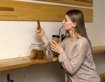 坐在咖啡馆饮用的咖啡的年轻美女吃曲奇饼 图库摄影