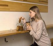 坐在咖啡馆饮用的咖啡的年轻美女吃曲奇饼 库存照片