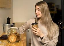 坐在咖啡馆饮用的咖啡的年轻美女吃曲奇饼 库存图片
