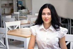 坐在咖啡馆,工作,研究地方的逗人喜爱的女孩 关闭画象照片 库存照片