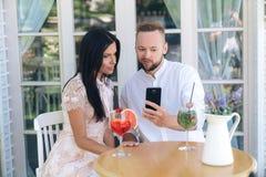 坐在咖啡馆,显示妇女在智能手机,女孩有趣的神色的一个人的一张桌上的特写镜头爱的夫妇照片 库存照片