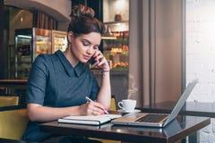 坐在咖啡馆,谈的oncell电话的桌上的灰色礼服的年轻女商人,当采取在笔记本时的笔记 库存照片