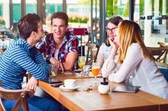 坐在咖啡馆,谈话和享用的小组青年人 库存照片