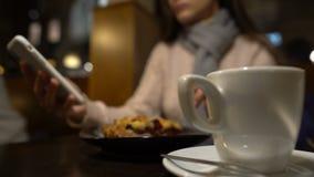 坐在咖啡馆,饮用的咖啡用饼和用完手机,关闭的夫人 影视素材