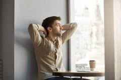 坐在咖啡馆,饮用的咖啡的可爱的年轻不剃须的人,看窗口用在他的头后的手,被用尽 免版税库存图片