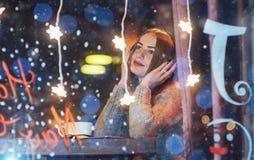 坐在咖啡馆,饮用的咖啡的年轻美丽的妇女 式样听到音乐 圣诞节,新年好,情人节, winte 免版税图库摄影
