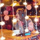 坐在咖啡馆,饮用的咖啡的年轻美丽的妇女 式样听到音乐 圣诞节,新年好,情人节, winte 库存图片