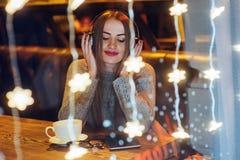 坐在咖啡馆,饮用的咖啡的年轻美丽的妇女 式样听到音乐 圣诞节,新年,情人节,冬天holi 库存照片