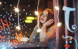 坐在咖啡馆,饮用的咖啡的年轻美丽的妇女 式样听到音乐 圣诞节,新年,情人节,冬天holi 免版税库存图片