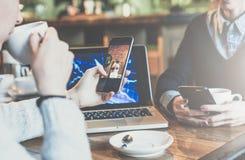 坐在咖啡馆,饮用的咖啡的桌上和使用智能手机的两个年轻女商人 在背景膝上型计算机 图库摄影