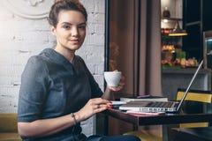 坐在咖啡馆,饮用的咖啡的桌上和看照相机的年轻女实业家 免版税图库摄影