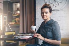 坐在咖啡馆,饮用的咖啡的桌上和看照相机的年轻女实业家 库存图片