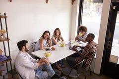 坐在咖啡馆,高的看法的五个成人朋友 免版税库存照片