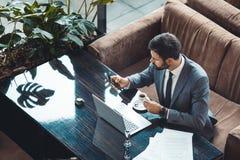 坐在商业中心餐馆的商人浏览社会媒介顶视图 免版税库存图片