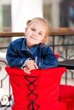 坐在商城的一个咖啡馆的逗人喜爱的小孩 库存照片