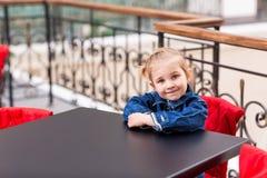 坐在商城的一个咖啡馆的逗人喜爱的小孩 库存图片