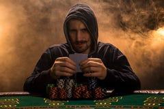坐在啤牌桌上的一个专业打牌者的画象 库存照片