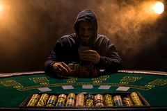 坐在啤牌桌上的一个专业打牌者的画象 库存图片