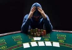 坐在啤牌桌上的一个专业打牌者的画象 免版税库存图片