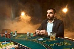 坐在啤牌桌上的西装的一个年轻人 人赌博 赌桌纸牌的球员 免版税库存照片